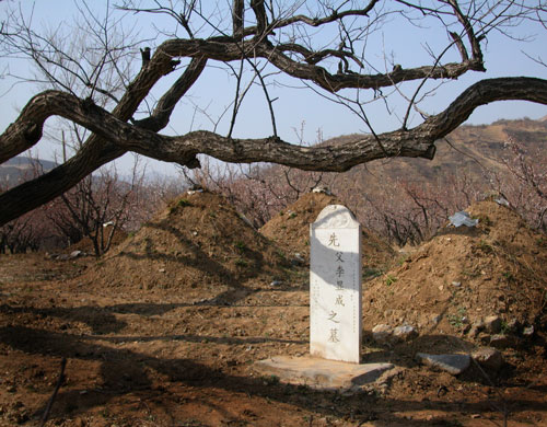 Lone headstone in shadow of the Great Wall.
