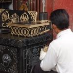 Tibetan man painting stove