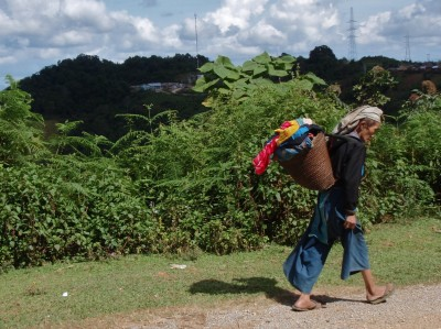 Member of on of 30 Hill Tribes, leaning into her load.