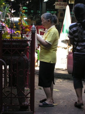Woman Making Offering At Market Shrine in Bangkok