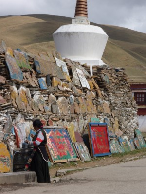 Tibetan woman walking past stupa in Litang Tibet